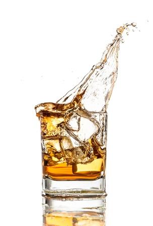 Whiskey glass with splash, isolated on white background photo