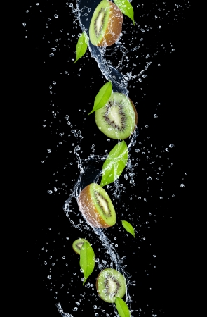 Kiwi slices in water splash, isolated on black background Stock Photo