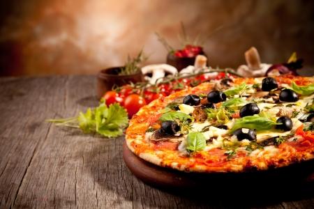 pizza: Heerlijke verse pizza geserveerd op een houten tafel
