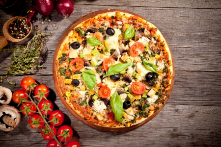 pizzas: Delicious fresh pizza served on wooden table Stock Photo