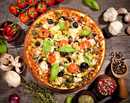 served: Delicious fresh pizza served on wooden table Stock Photo