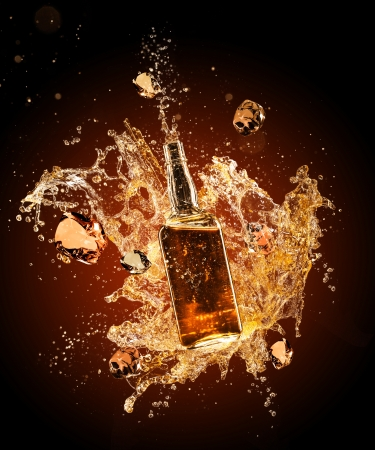 spatter: Isolated shot of whiskey splashing around bottler on black background Stock Photo
