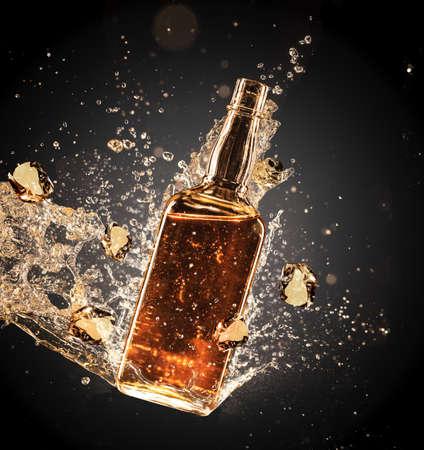 scotch: Geïsoleerde schot van whisky spatten rond bottelaar op zwarte achtergrond