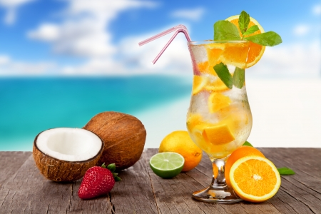Summer cocktail with pieces of fruit on wooden table  Blur beach on background photo
