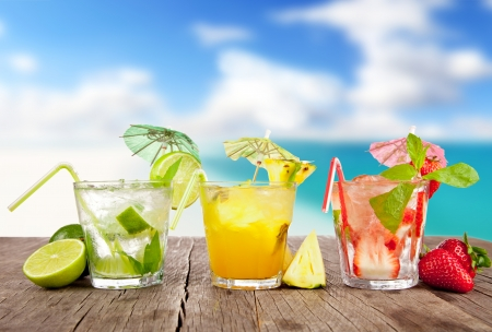 cocktail glasses: Summer cocktails with pieces of fruit on wooden table. Blur beach on background Stock Photo
