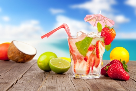 Strawberry mojito with pieces of fruit on wooden table. Blur beach on background photo