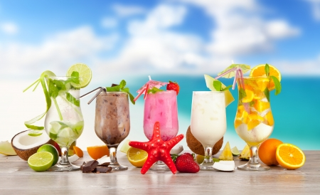 Summer cocktails with pieces of fruit on wooden table. Blur beach on background 免版税图像