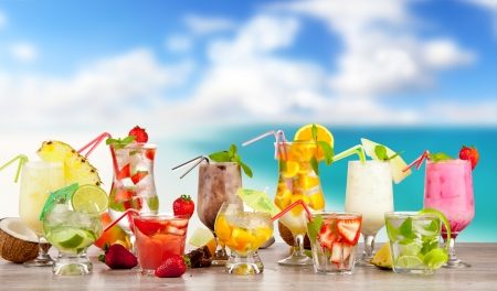 Summer cocktails with pieces of fruit on wooden table. Blur beach on background Stock Photo - 19433994