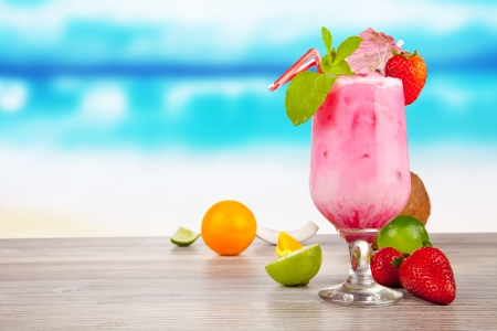 Summer cocktail with pieces of fruit on wooden table. Blur beach on background photo