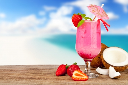 Summer cocktail with pieces of fruit on wooden table. Blur beach on background Foto de archivo