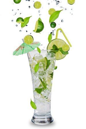Fresh mojito drink with falling limes into glass. Isolated on white background photo