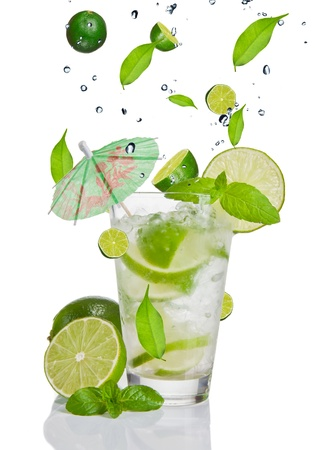 color mixing: Fresh mojito drink with falling limes into glass. Isolated on white background