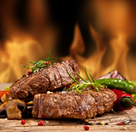 charbroiled: Delicious beef steakes on wood Stock Photo