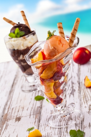 Delicious ice cream cups on wooden table and blur beach on background