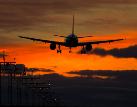 plane landing: Big jet plane landing on runway in evening