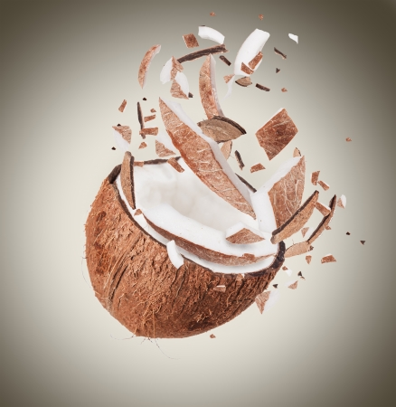 Coconut in motion with breaking pieces photo
