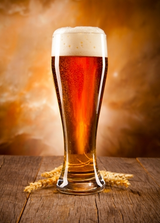 Glass of beer on woden table Imagens