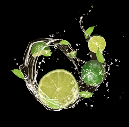 Fresh limes in water splash, isolated on black background photo
