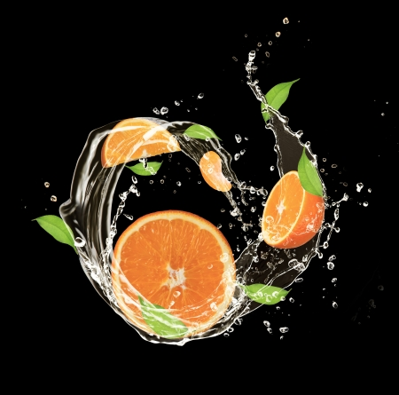 Fresh oranges in water splash, isolated on black background photo