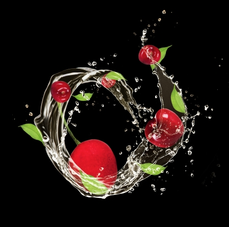 Fresh cherries in water splash, isolated on black background photo