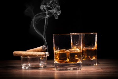 Whiskey drinks with smoking cigars on wooden table photo