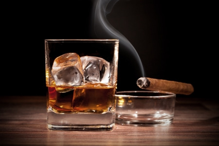 Whiskey drink with smoking cigar on wooden table photo