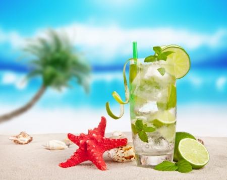 Mojito drink on beach with sea shells photo