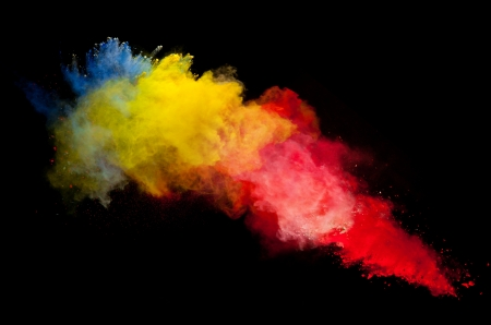 sprays: Freeze motion of colored dust explosion isolated on black background Stock Photo