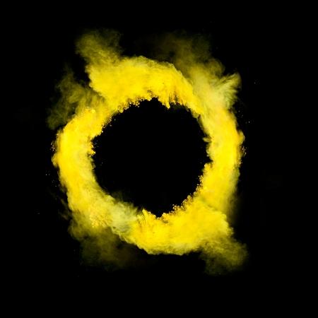 splash paint: Freeze motion of yellow dust in round shape isolated on black background