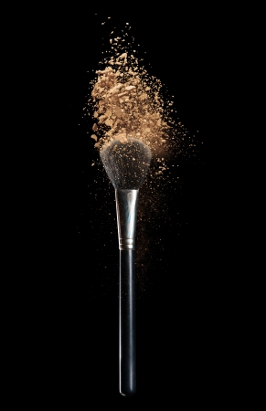 Isolated make-up powder with brush on black background photo