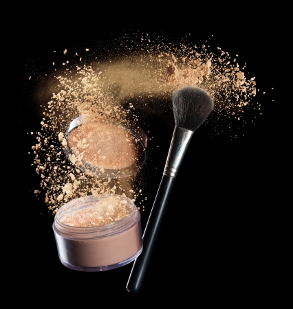 Isolated make-up powder with brush on black background Фото со стока