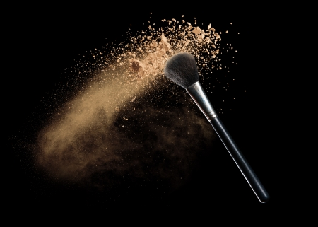 Isolated make-up powder with brush on black background Imagens