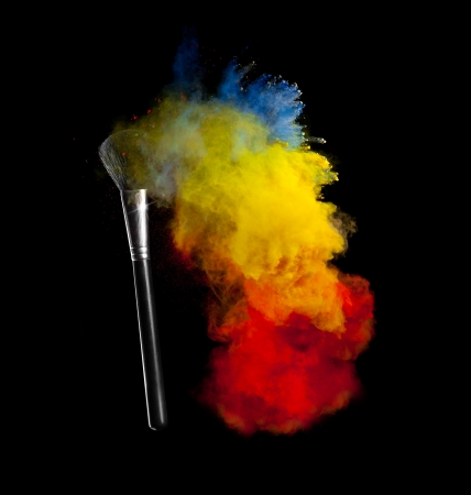 Freeze motion of colored dust explosion with brush, isolated on black background photo