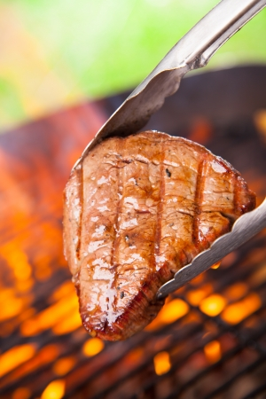 Delicious beef steaks on grill photo