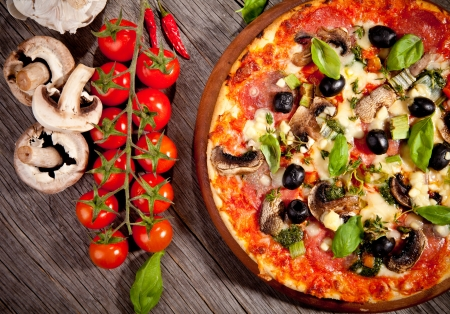 pizza ingredients: Delicious fresh pizza served on wooden table Stock Photo