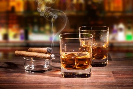 Beber whisky con el cigarro fumar en mesa de madera Foto de archivo