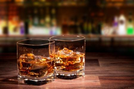 tomando alcohol: Copas de whisky en la mesa de madera con el desenfoque de bar en el fondo Foto de archivo