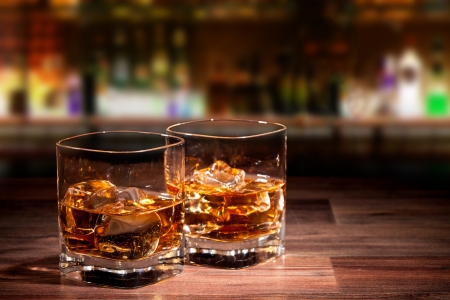 whiskey glass: Whiskey drinks on wooden table with blur bar on background