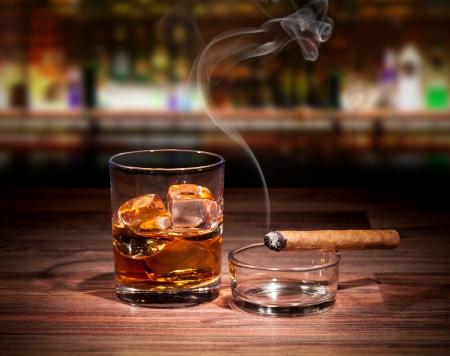 나무 테이블에 흡연 시가와 위스키 음료
