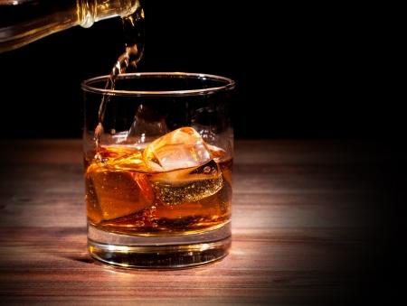 botella de whisky: Beber whisky en la mesa de madera, aislado en el fondo negro