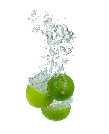 Fresh lime falling into water, isolated on white background photo