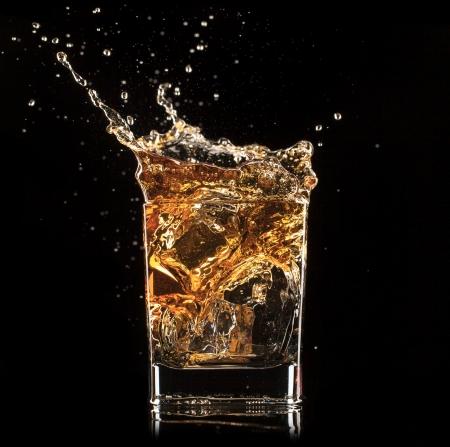 黒い背景にスプラッシュとウイスキーのショットを分離 写真素材