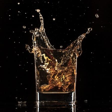 黒の背景にスプラッシュとウイスキーの分離ショット 写真素材