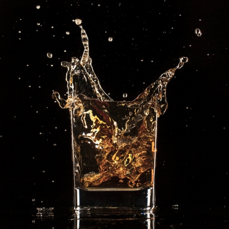 Isolated shot of whiskey with splash on black background photo