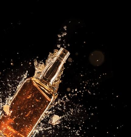 botella de licor: Disparo aislado de whisky con salpicaduras en el fondo negro Foto de archivo