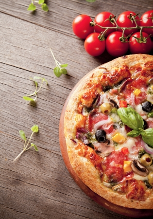 rustic food: Delicious fresh pizza served on wooden table Stock Photo