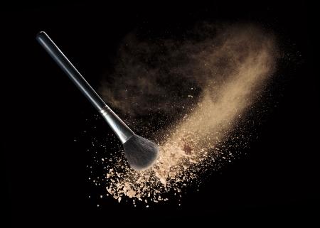 black powder: Isolated make-up powder with brush on black background Stock Photo