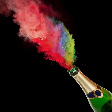Bottiglia di champagne con spruzzi di colore su sfondo nero