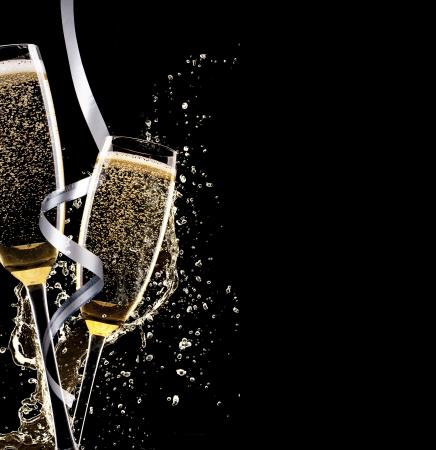 Glazen champagne met splash, geïsoleerd op zwarte achtergrond Stockfoto