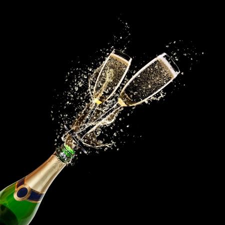 Glazen champagne met fles, geïsoleerd op zwarte achtergrond Stockfoto